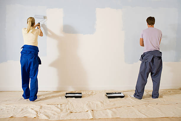 Jeune couple qui repeint les murs de son appartement